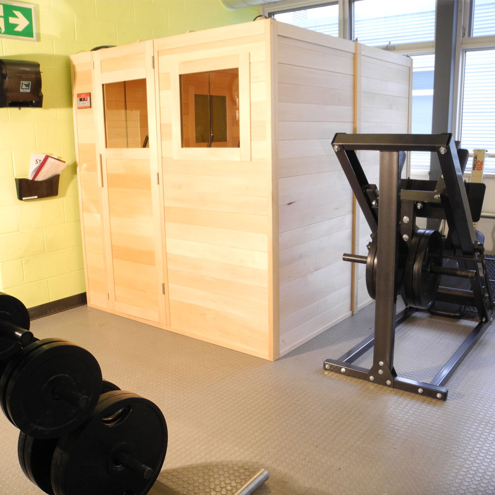 A picture of a custom infrared sauna built inside of a home gym