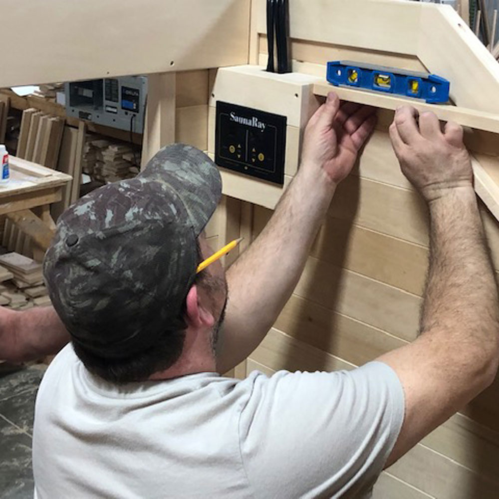 A man working with a level reviewing a custom infrared sauna, made in Canadian Basswood by SaunaRay