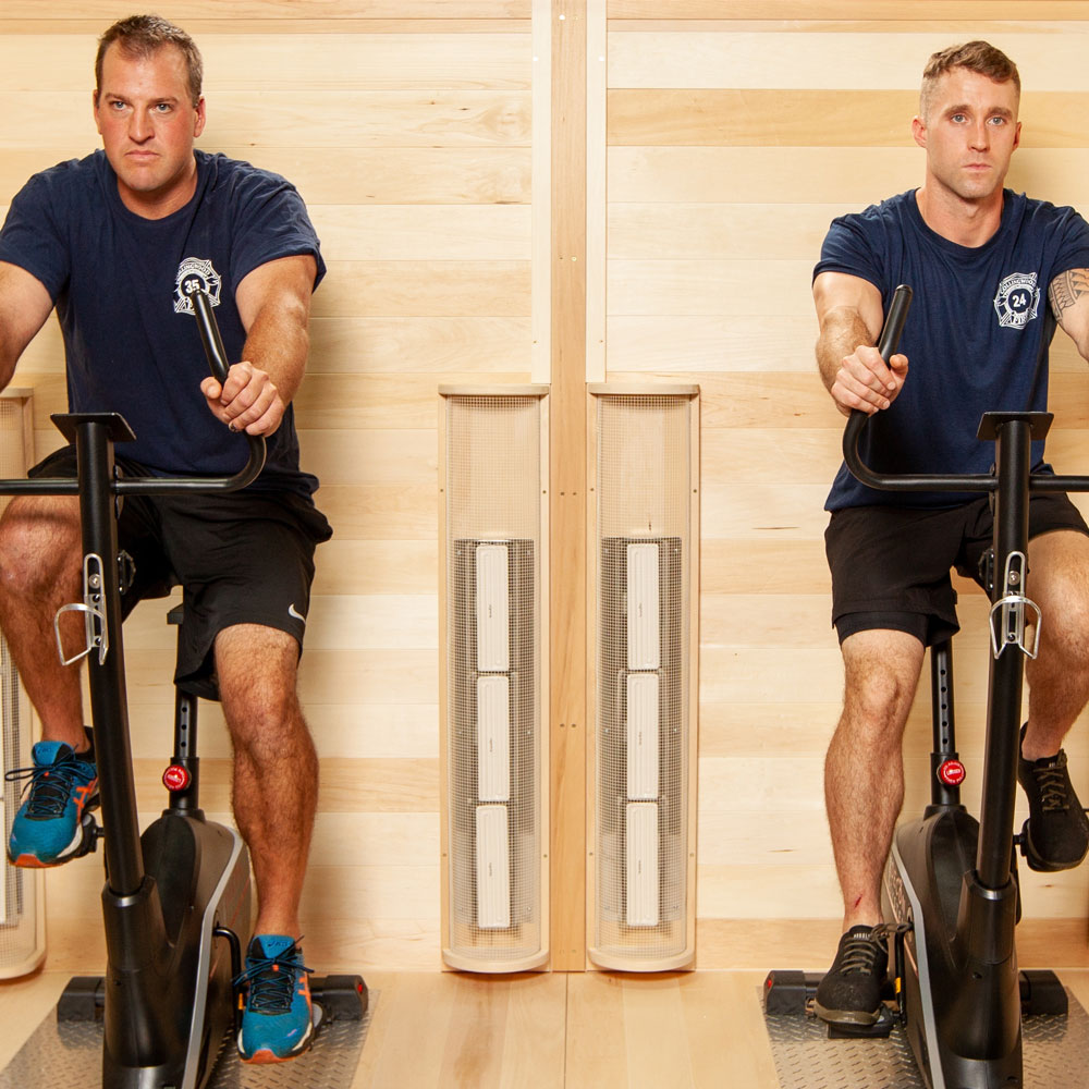 A picture of a custom built infrared sauna and 2 firemen on exercise bikes