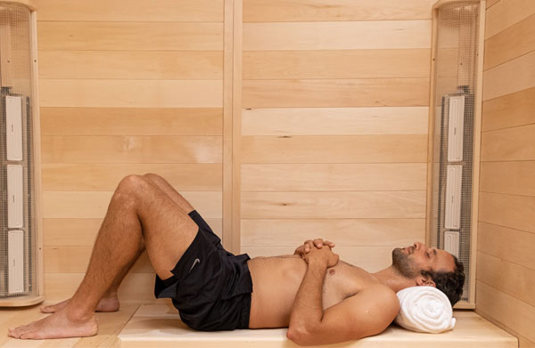 A man lying down inside a 3 person infrared sauna made by SaunaRay
