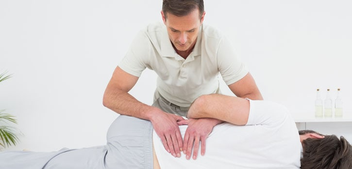 A picture of a chiropractor working on a patients lower back