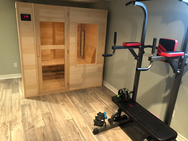 a picture of a SaunaRay far infrared sauna set up within an customers home gym